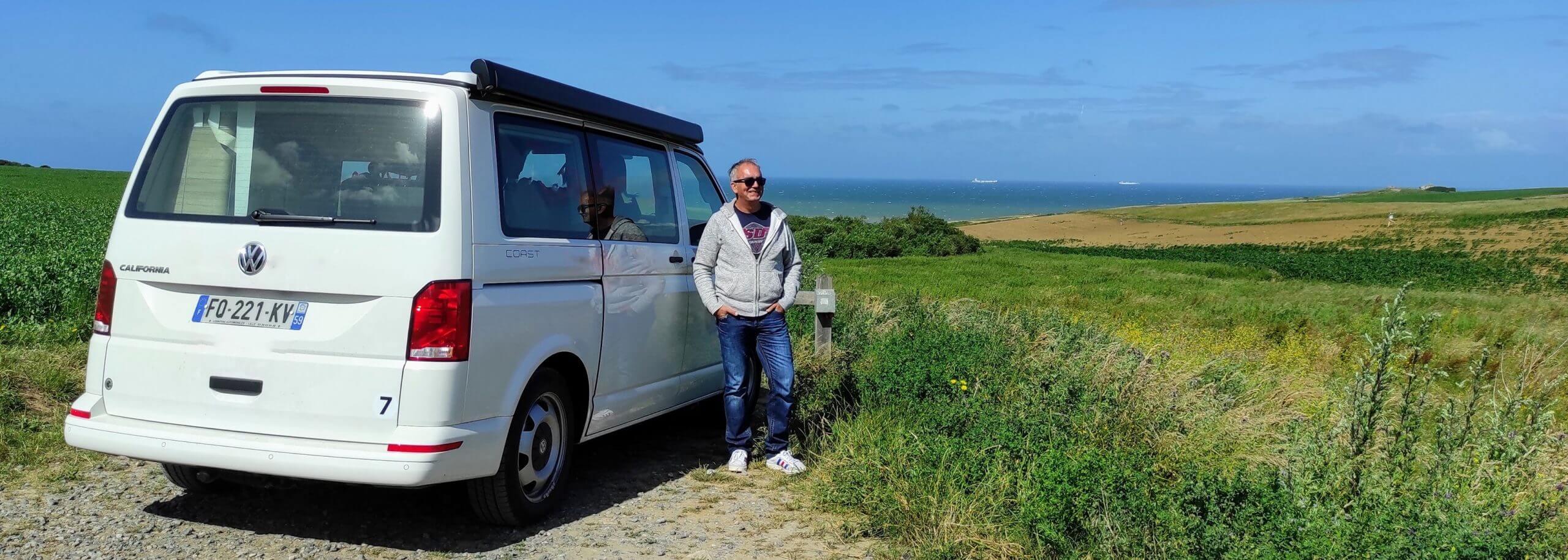 Notre histoire : Christophe à côté d'un van aménagé face à la mer.