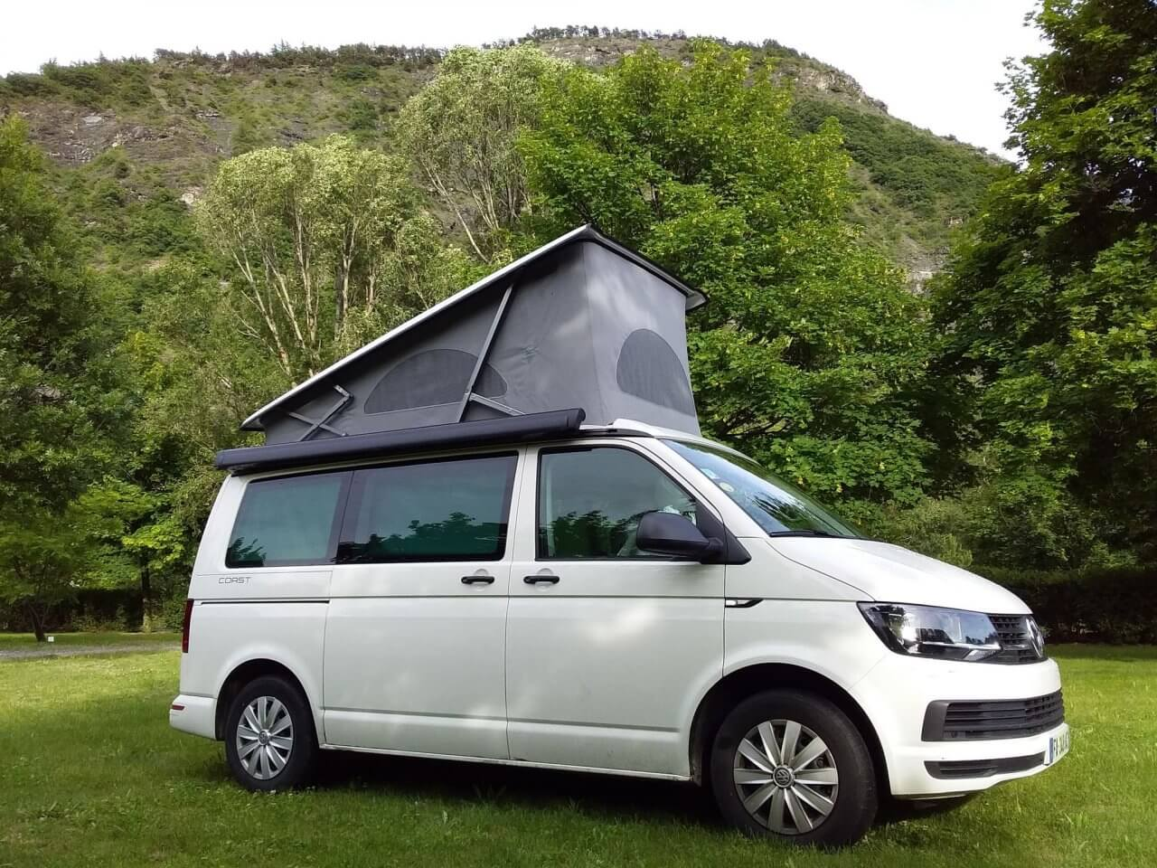 Location de Van aménagé Lille Valenciennes Mybiglittlevan Volkswagen California Coast 6.1 blanc toit relevé face à la montagne